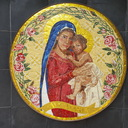 "The Madonna of Consolation is tender and caring as she holds her infant Jesus.  The roses In different stages of  blooming—buds, full bloom and finally, dying—are symbolic of the lyrics of the song Eye has not Seen, ""Our lives are but a single breath; we flower then we fade.""  The top flowerless vines are a foreshadowing of the crown of thorns."